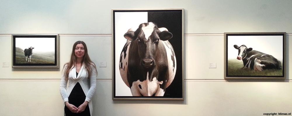 Ik sta bij mijn drie koeien schilderijen.